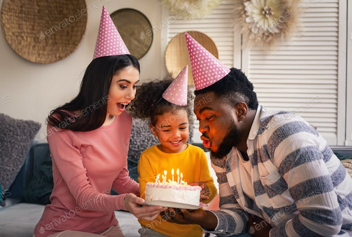 Father and mother help daughter blow out candles
