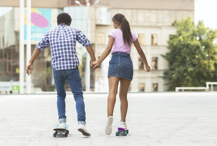 Happy african teenagers riding skateboards and holding hands