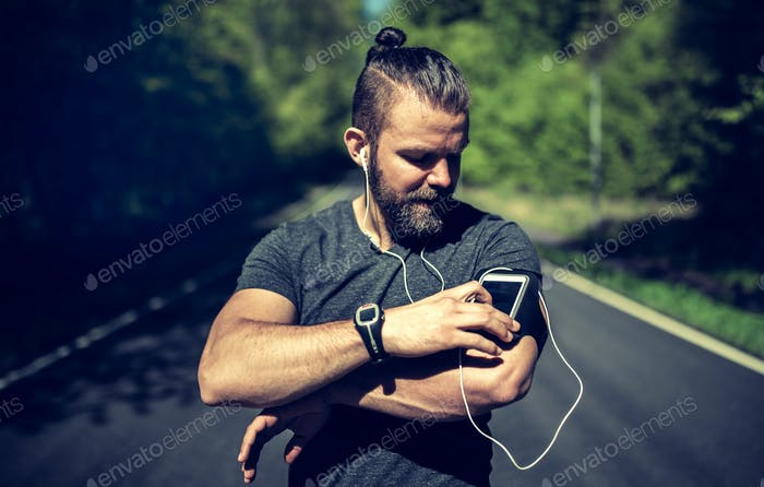 Fit young man queueing up his playlist before a run