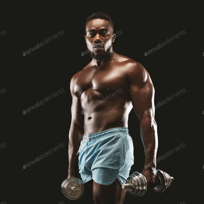 Portrait of african american sportsman holding dumbbells