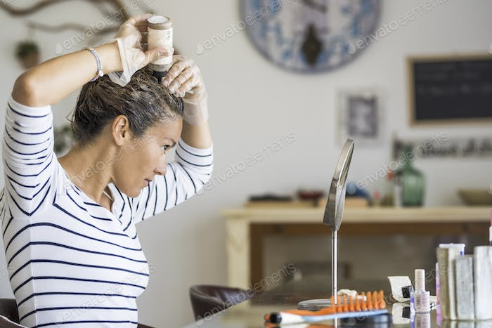Young beautiful woman colouring her hair at home herself with chemical products