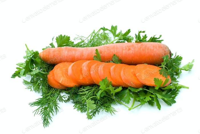 Ganze Karotte und ein paar Scheiben über etwas Dill und Petersilie