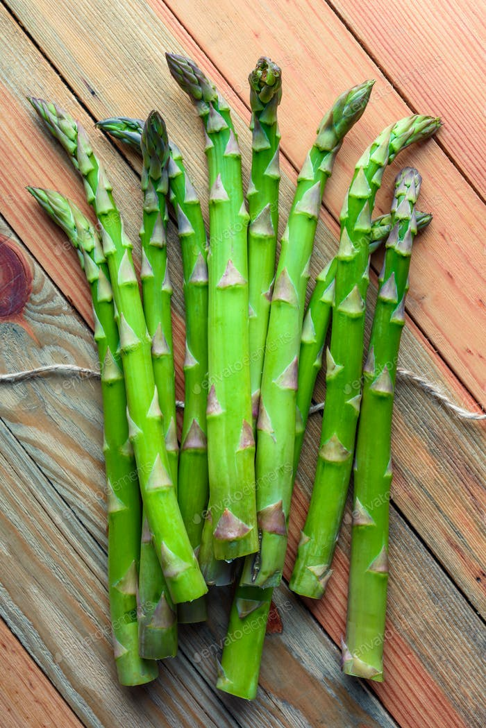 Green asparagus sprout on wooden board