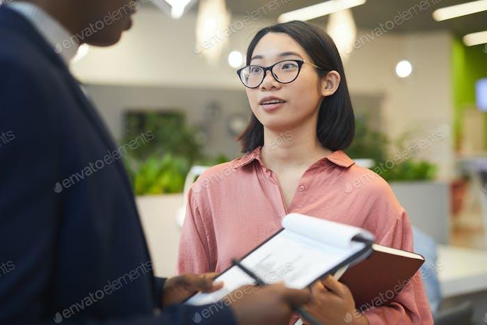 Mujer de negocios asiática hablando con el jefe