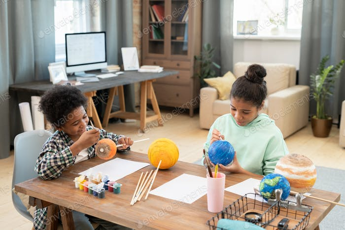 Two adorable siblings of elementary age painting planets while sitting by table
