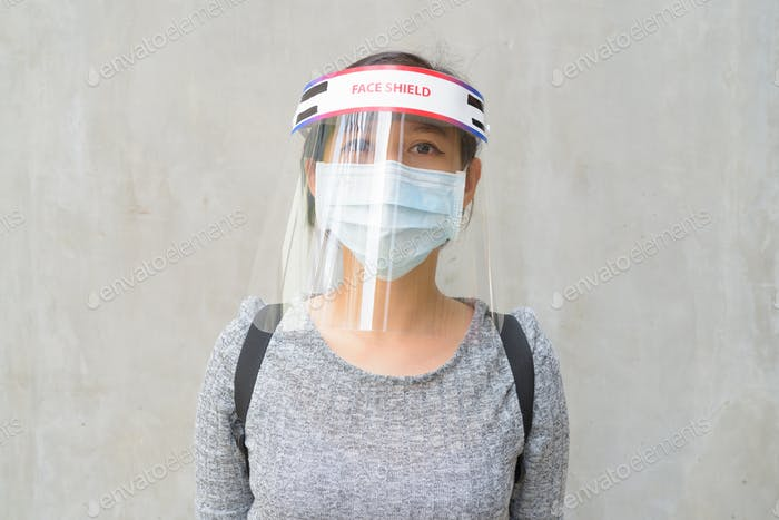 Young Asian woman wearing mask and face shield for protection from corona virus outbreak outdoors