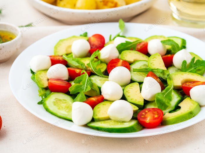 Fresh salad with tomatoes cucumbers arugula mozzarella and avocado. Oil with spices