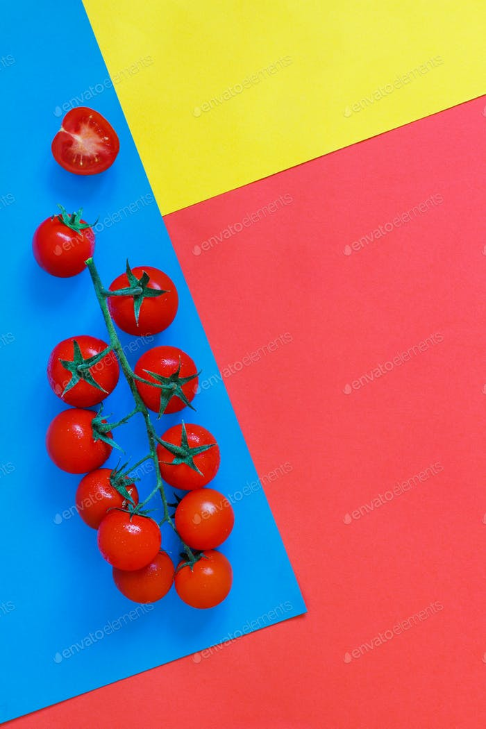 Cherry tomatoes on a blue, coral red and yellow background