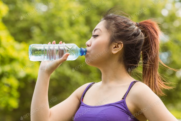Healthy and beautiful young woman drinking water in park