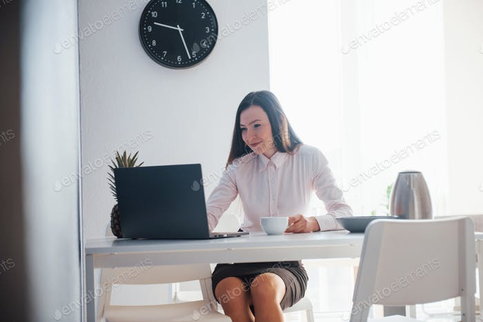 New working day. Young businesswoman with black hair in official clothes at her home