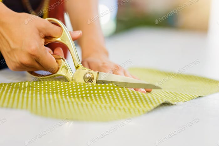 Hands of unrecognizable tailor woman cutting fabric with scissors
