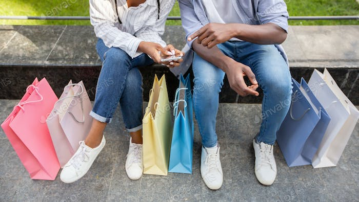 Share with followers emotions and photo of shopping. African american couple making photo of