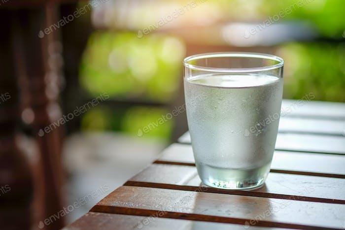 Wasserglas auf Holztisch.