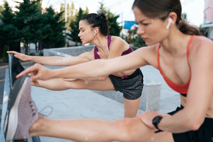 Fit and sporty young women doing stretching in the city.