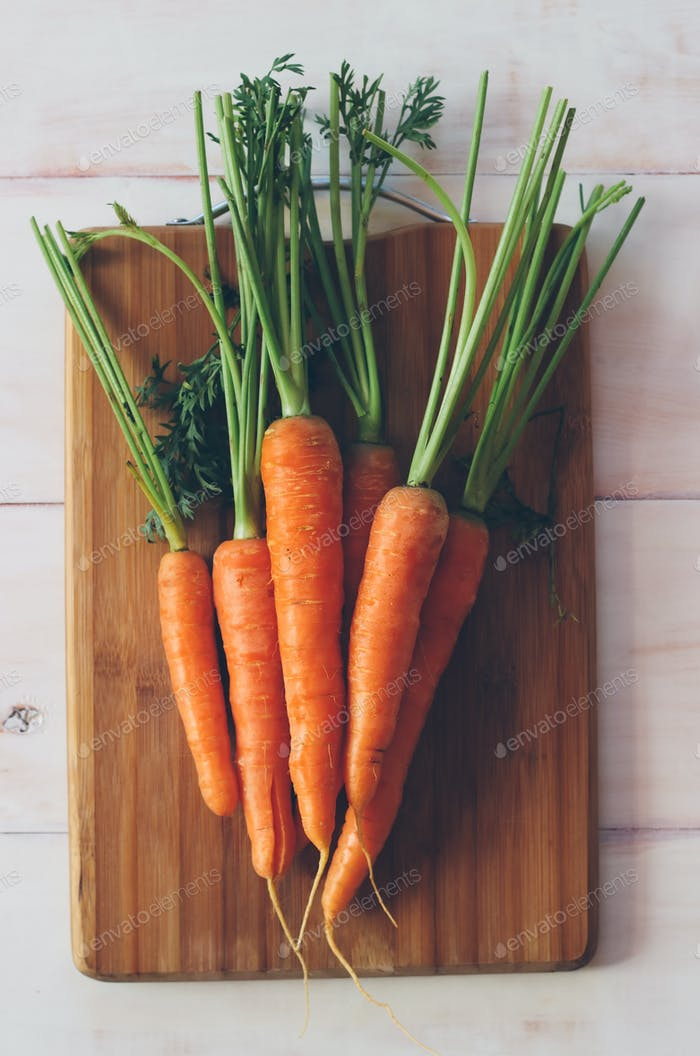 Fresh organic carrots on a wooden background