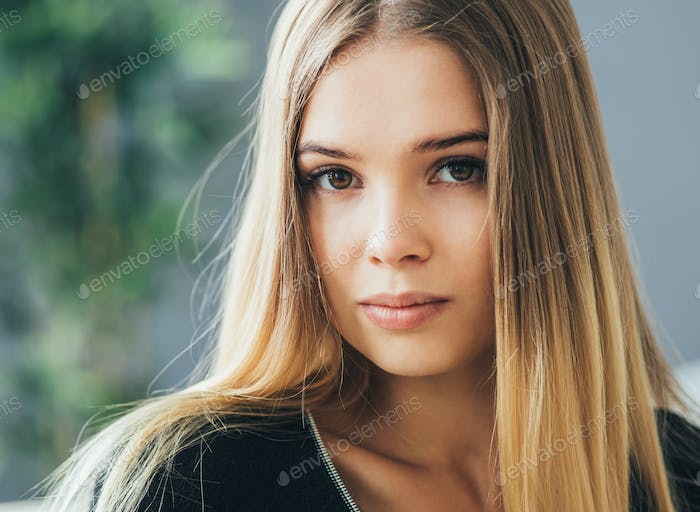 Woman natural indoor portrait, blonde long hair cute face