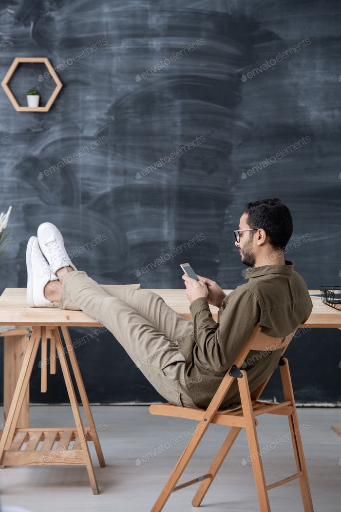Young casual employee keeping legs on table while scrolling in smartphone