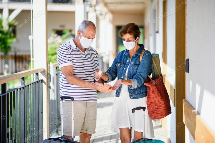 Senior couple with face masks and luggage outside apartment on holiday