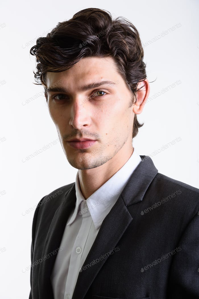 Studio shot of young handsome businessman looking at camera