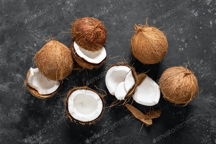 Coconuts cracked and whole on black background, top view