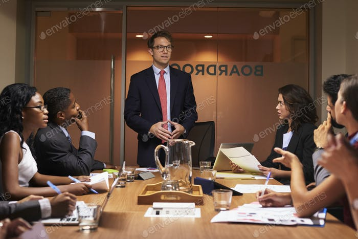 White businessman standing to address colleagues at meeting