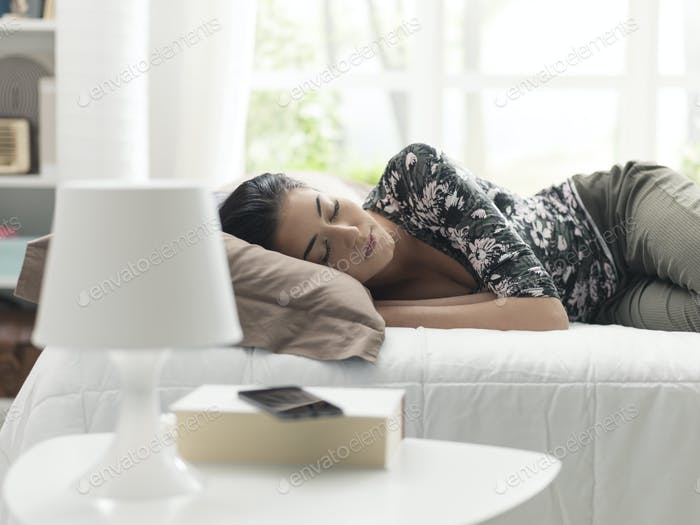 Young beautiful woman napping on the bed