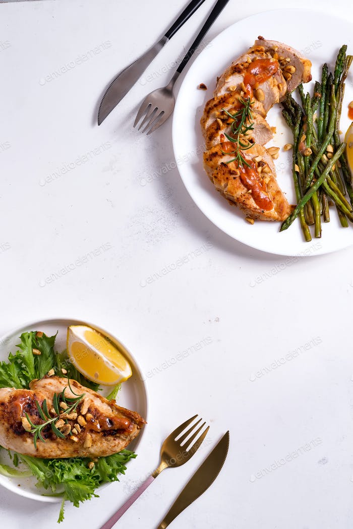 Grilled chicken breast with grilled asparagus and lemon slice on stone background . Paleo diet