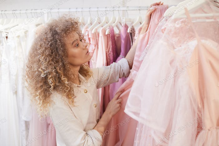 Young Woman Choosing Dress in Clothing Store