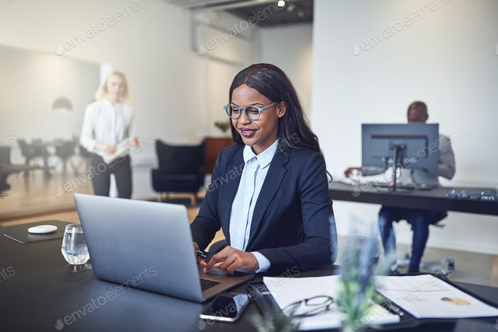 Smiling African American businesswoman sitting at work using a laptop