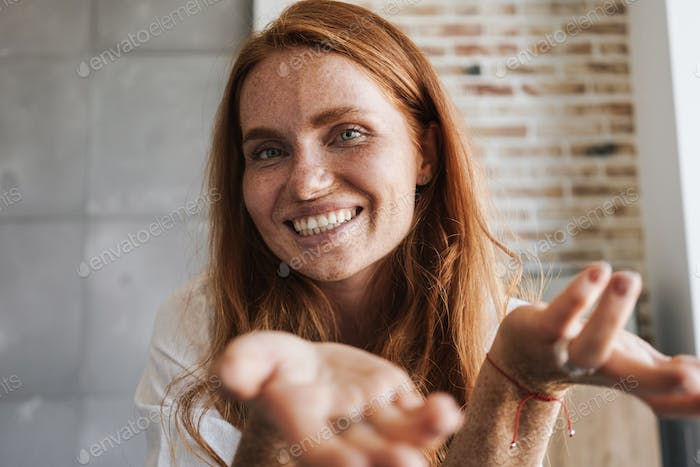 Image of happy ginger woman with freckles smiling and showing copyspace