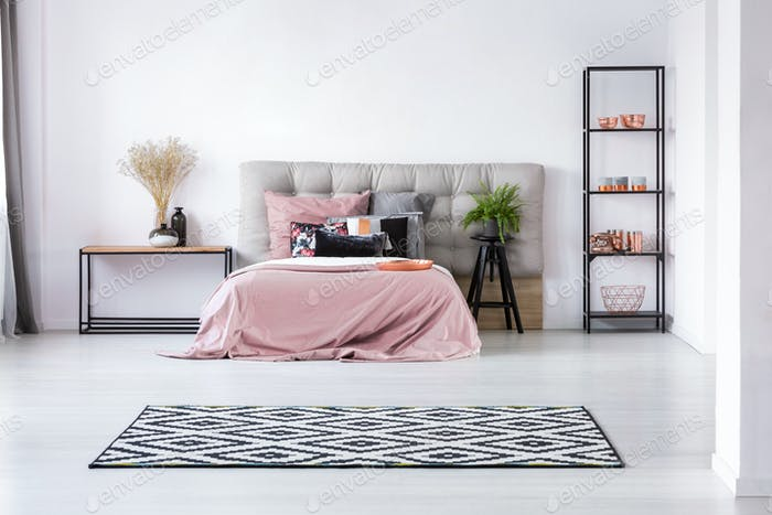 Trendy black and white rug on white floor of cozy bedroom interior