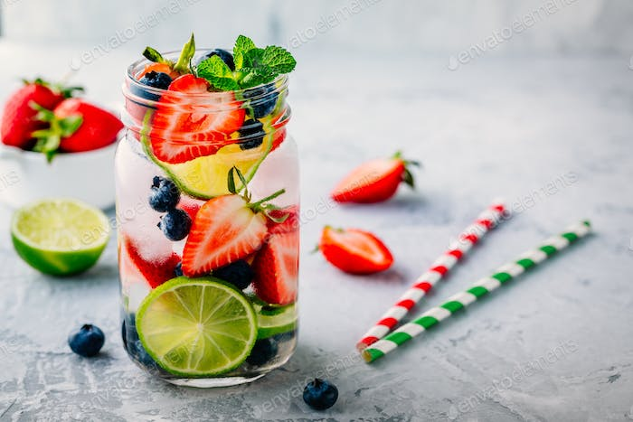 Infused detox water with blueberry, strawberry, lime and mint. Ice cold summer cocktail or lemonade.
