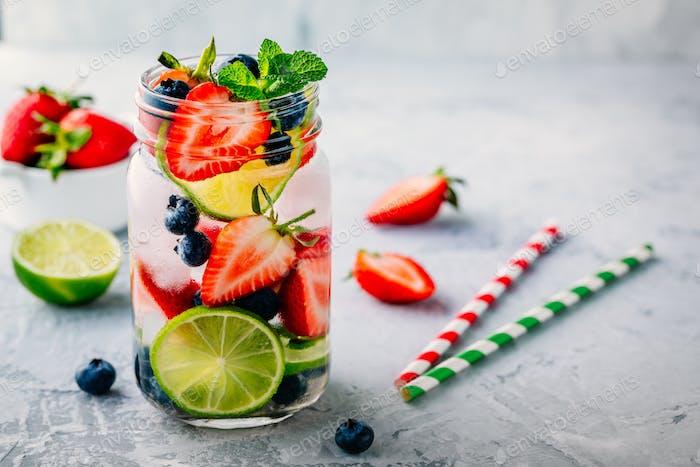 Infusion Detox Wasser mit Heidelbeere, Erdbeere, Limette und Minze. Eiskalter Sommercocktail oder Limonade.