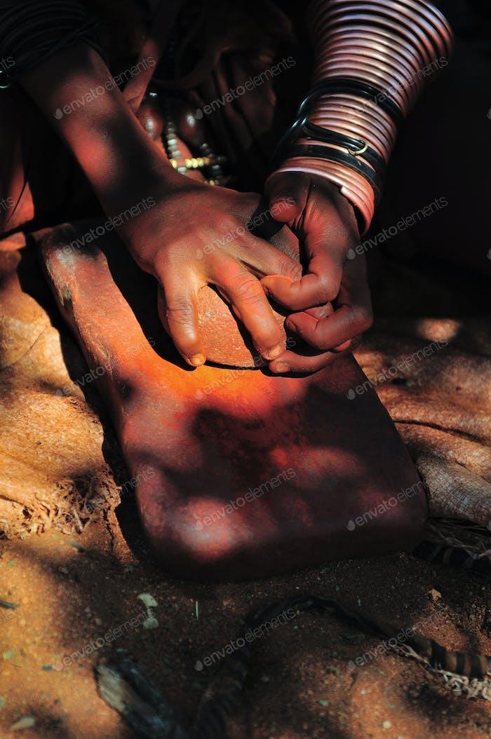 Himba woman grinding ochre