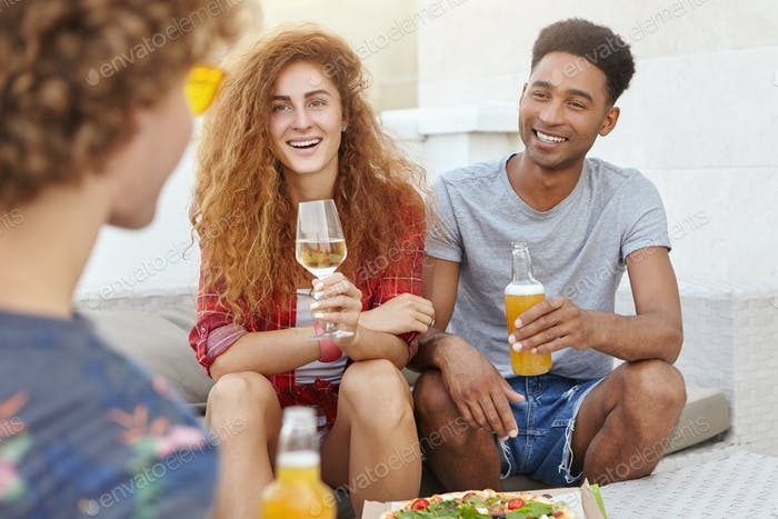 Portrait of youngsters gathering together at cafe, eatting delicious pizza, drinking wine and beer h