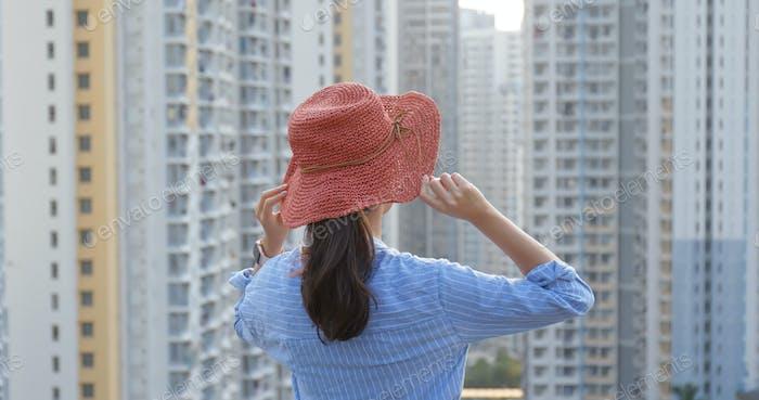 Frau trägt roten Strohhut und schauen Sie sich in der Stadt mit Bauarchitektur Hintergrund um