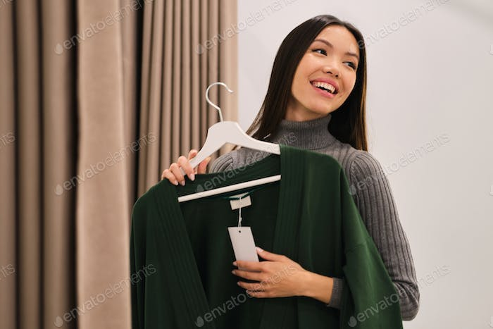 Pretty cheerful Asian girl happily trying on cardigan in fashion store