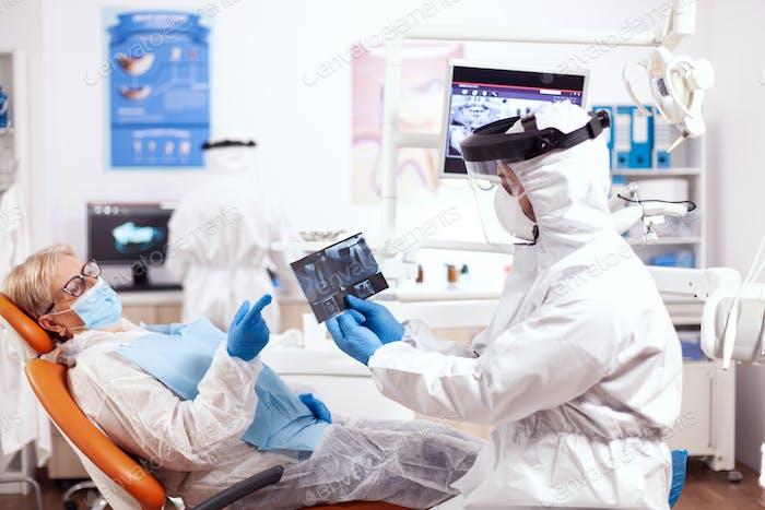 Stomatolog in safety gear agasint coronavirus holding x-ray