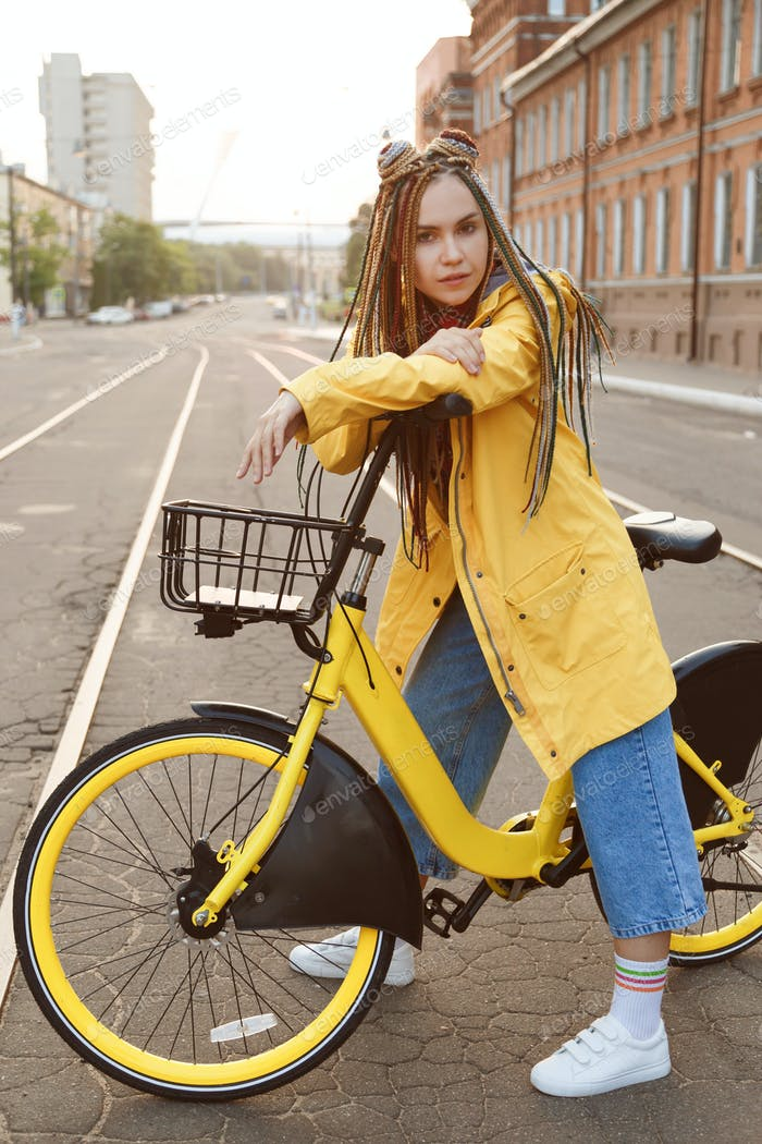 Young woman wearing yellow coat and colored pigtails, riding bike in city