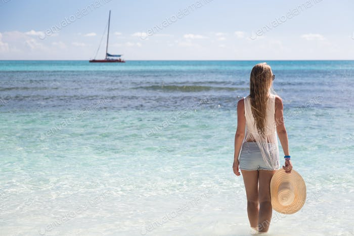 Girl stand in water looking to the sea, Saona