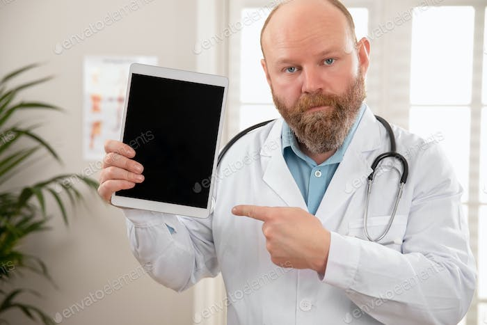 Serious adult male doctor showing a digital image or report on a tablet