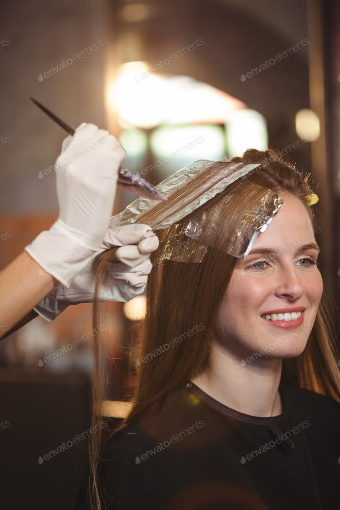 Hairdresser dyeing hair of her client