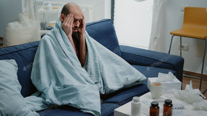 Unwell man with headache rubbing temples and feeling sick