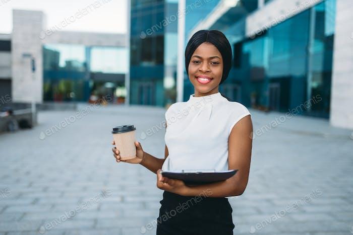 Geschäftsfrau mit Kaffeetasse und Notizblock
