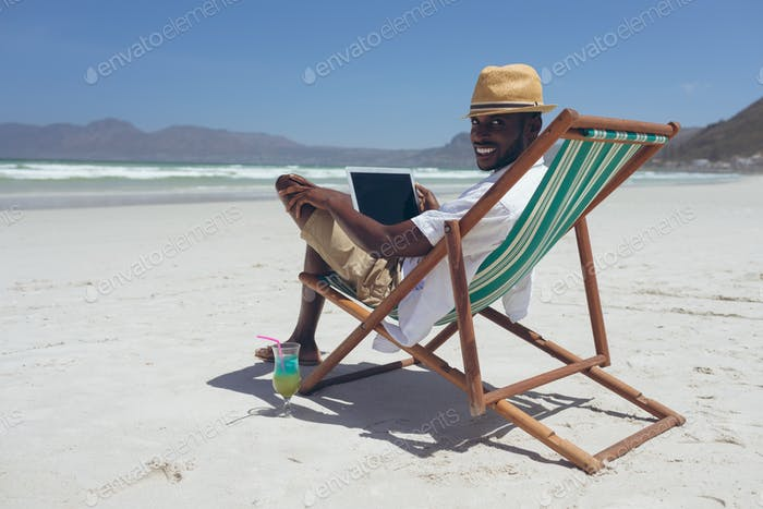 Man using laptop while sitting on sun lounger at beach on sunny day