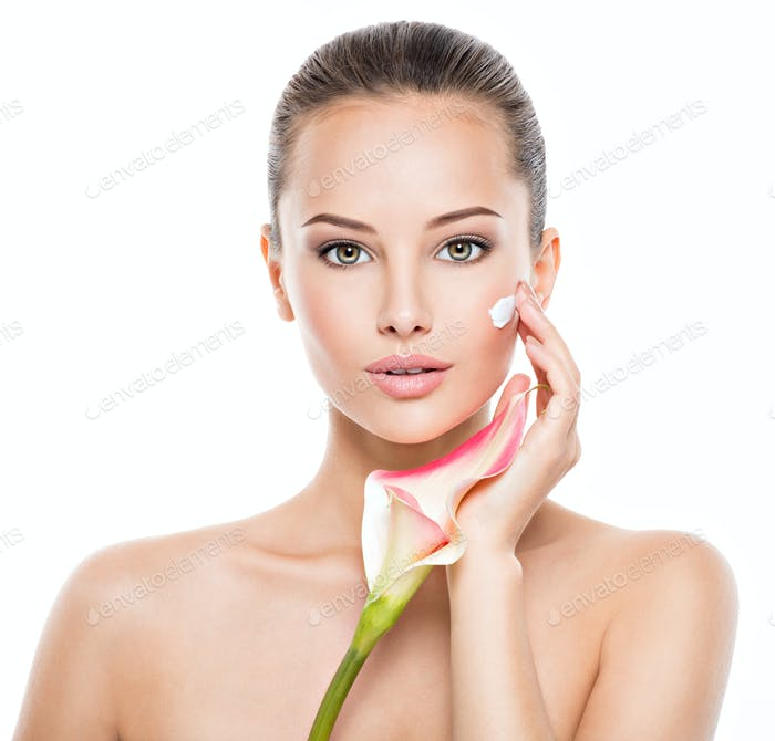 Woman applying cosmetic  cream on a face.