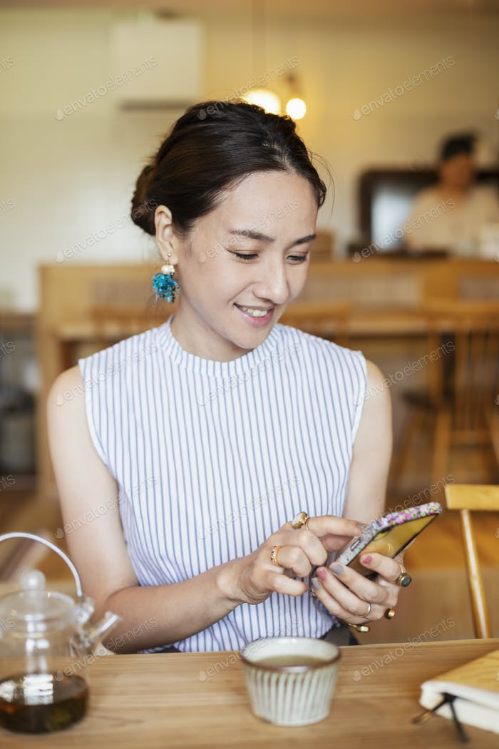 Japanese woman sitting at a table in a vegetarian cafe, using mobile phone.
