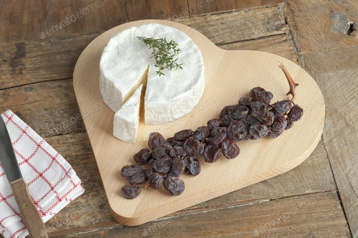 Camembert cheese with a twig of muscat raisins