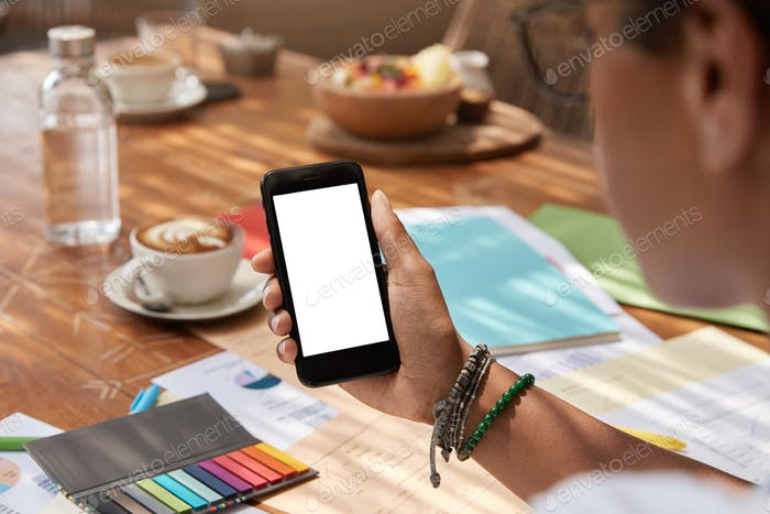 Неузнаваемая этническая молодая женщина держит современный смартфон с пустым экраном, синхронизирует мультимедиа
