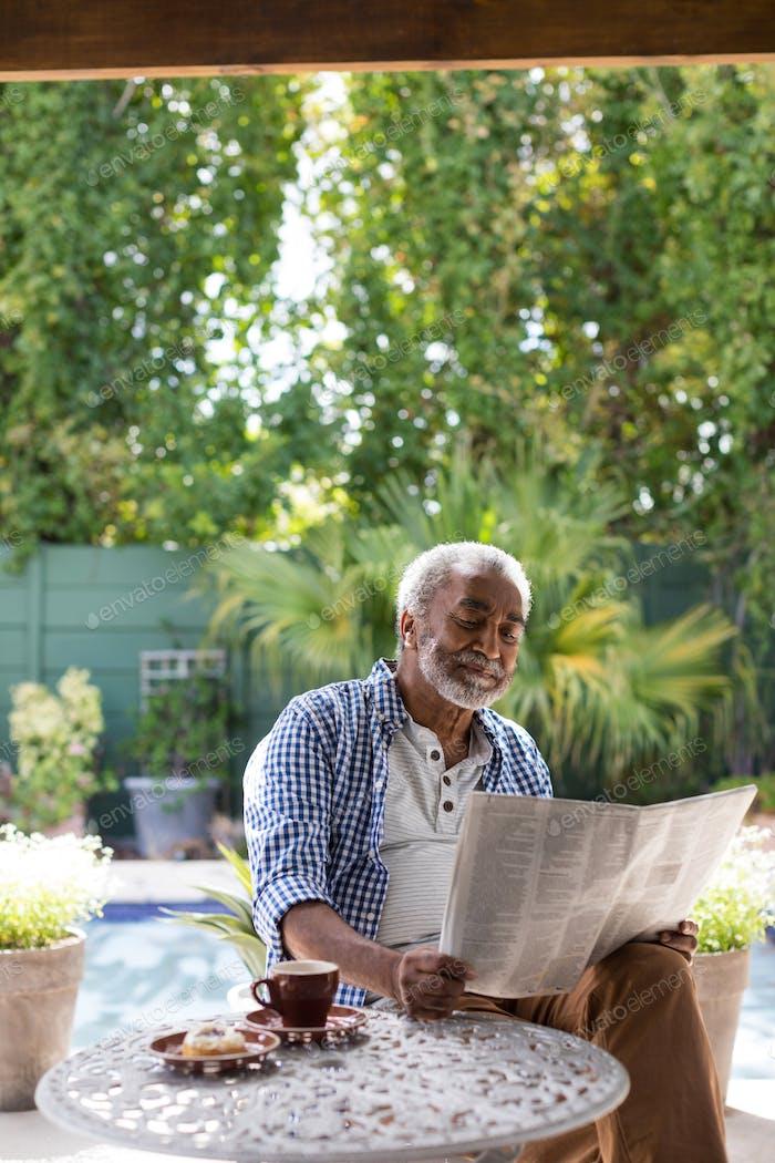 Senior man reading newspaper at table